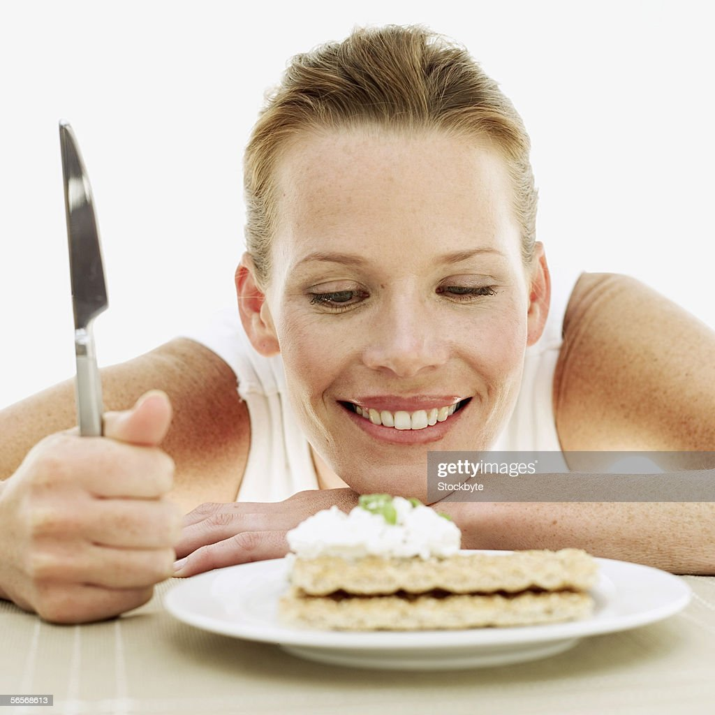 young woman looking at a plate of sesame seed crackers with cream : Stock Photo