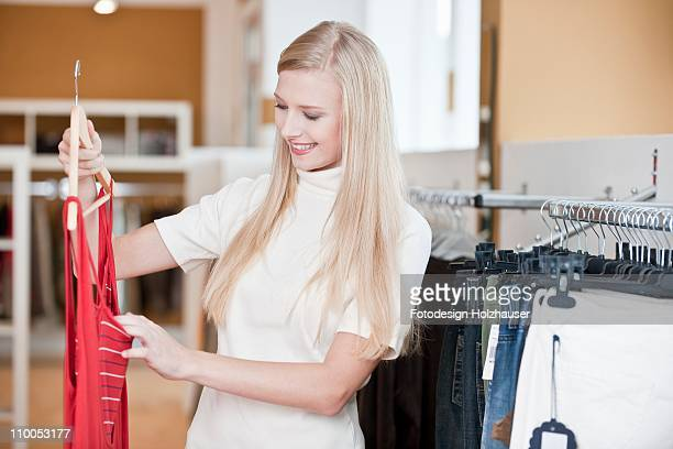Young woman looking at a top in a clothes shop