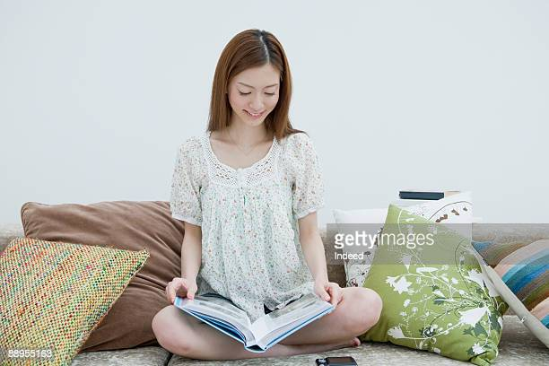 young woman looking at album on sofa, smiling - 下を向く ストックフォトと画像