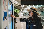 空港の情報画面を見ている若い女性