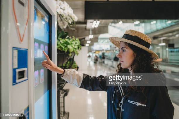 young woman looking at an information screen at the airport - touch sensitive stock pictures, royalty-free photos & images