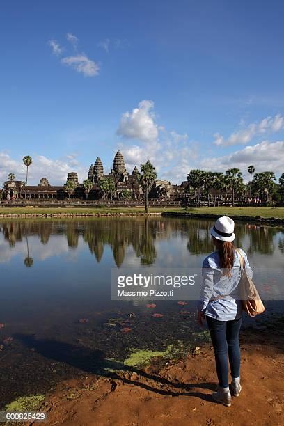 Young woman looking at Angkor Wat temple