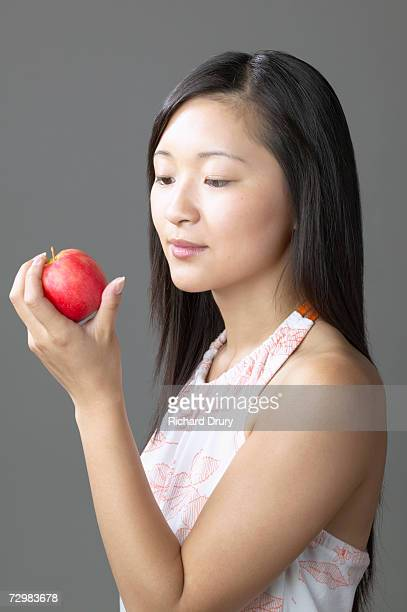 Young woman looking at apple in hand