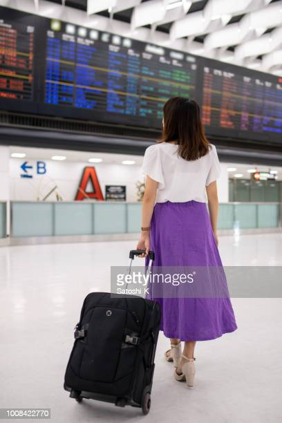 young woman looking at arrival departure board in airport - narita stock pictures, royalty-free photos & images