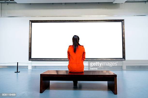 Young woman looking at artwork