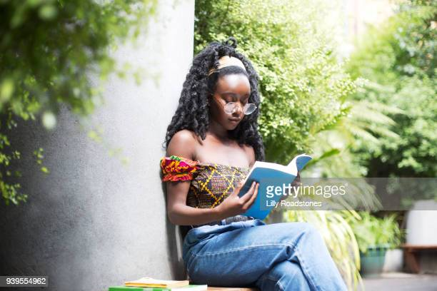 Young woman looking at book in city garden