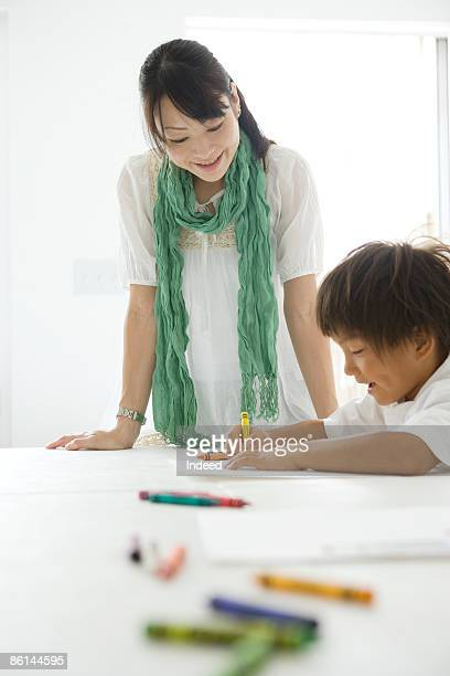 Young woman looking at boy's drawing, smiling