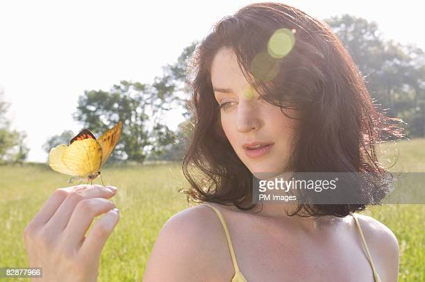 Young woman looking at butterfly on her hand