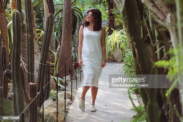 Young Woman Looking At Cactus While Walking In Botanical Garden