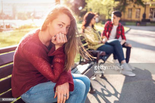 jovem mulher olhando pra câmera e sentada sozinha no banco do parque. - malícia - fotografias e filmes do acervo