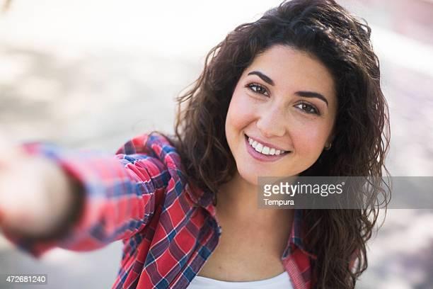 Jeune femme regardant la caméra et souriant.
