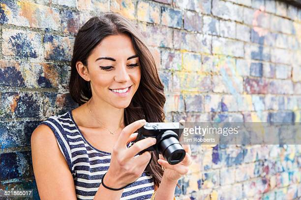 Young woman looking at camera screen.