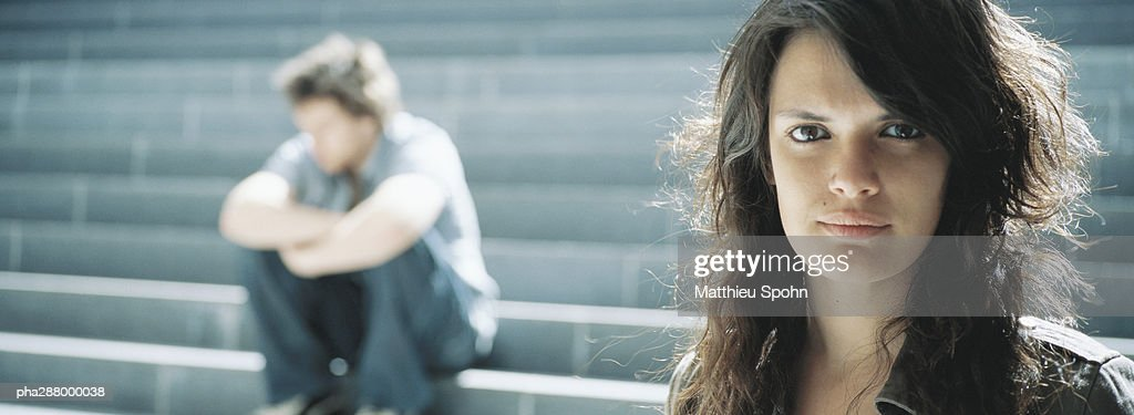 Young woman looking at camera, young man sitting in background : Stockfoto