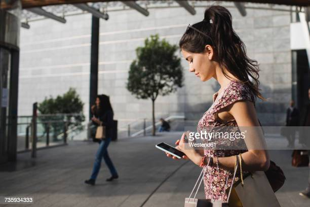 young woman looking at cell phone in the city - zuid europese etniciteit stockfoto's en -beelden