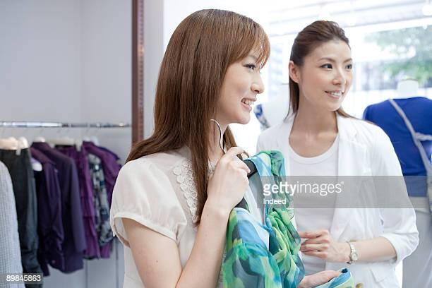 Young woman looking at cloth with shop assistant
