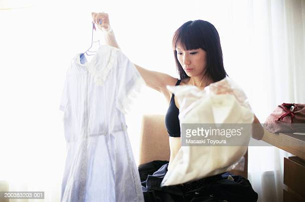 Young woman looking at clothes in room
