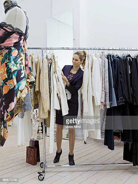 young woman looking at clothes in store