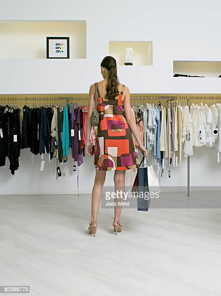 young woman looking at clothes in store, rear view