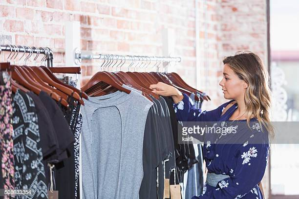 Young woman looking at clothing on racks in store