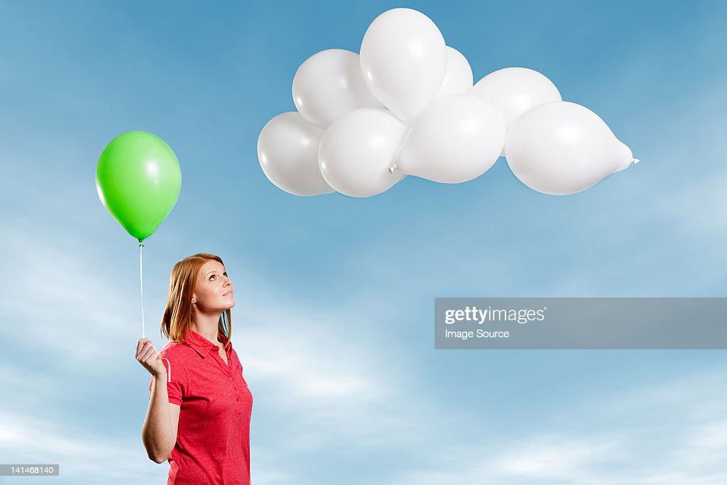 Young woman looking at cloud made of balloons : Stock Photo