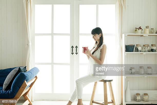 young woman looking at coffee cup by window - 椅子 ストックフォトと画像