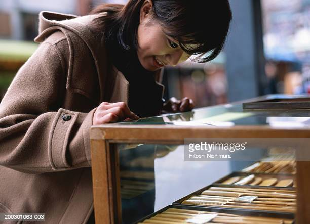 Young woman looking at combs in shop, outdoors