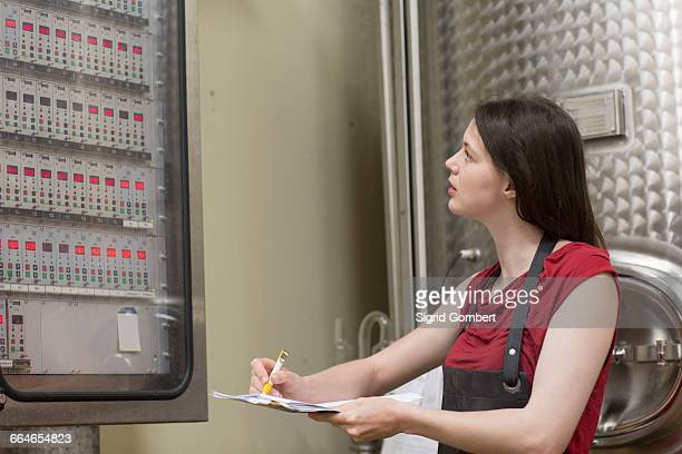 young woman looking at control panel in wine cellar - sigrid gombert - fotografias e filmes do acervo