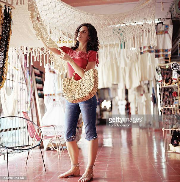 Young woman looking at crocheted shawl in shop