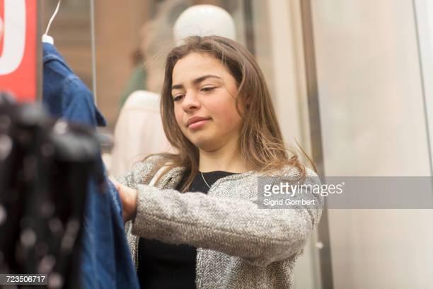 young woman looking at denim jacket on market stall - sigrid gombert - fotografias e filmes do acervo