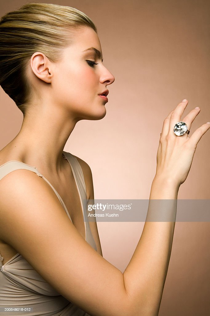 Young woman looking at diamond ring, close-up : Stock Photo