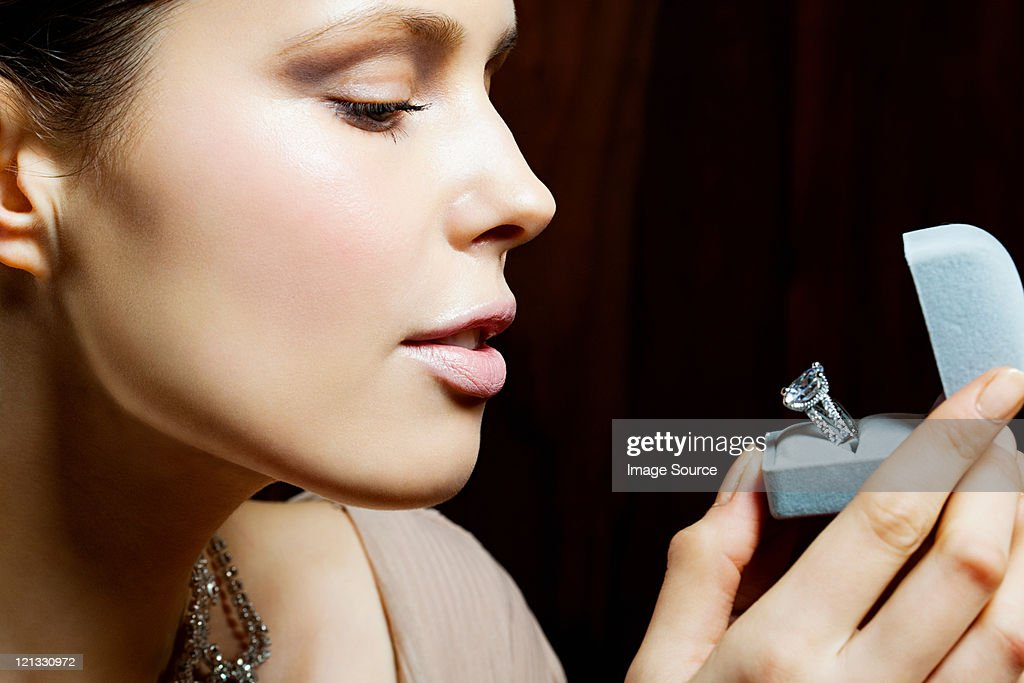 Young woman looking at engagement ring in box : Stock Photo