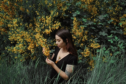 Young Woman Looking At Flowering Plants - gettyimageskorea