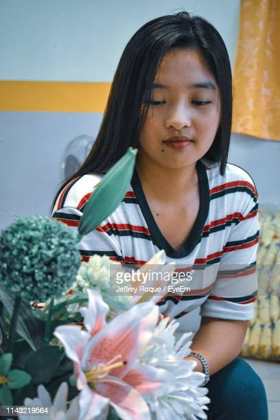 young woman looking at flowers - jeffrey roque stock photos and pictures