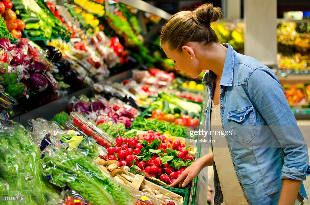 A young woman looking at fresh vegetables in the supermarket : Stockfoto