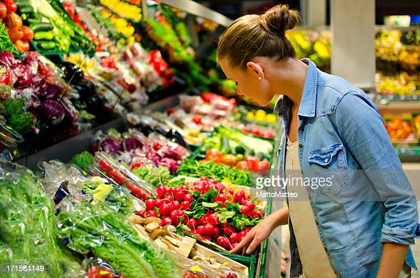 a young woman looking at fresh vegetables in the supermarket - freshness stockfoto's en -beelden