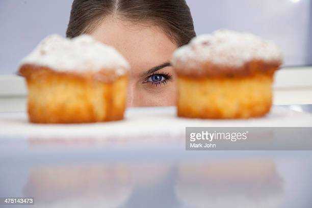 young woman looking at freshly bakes cakes - focus on background stock pictures, royalty-free photos & images