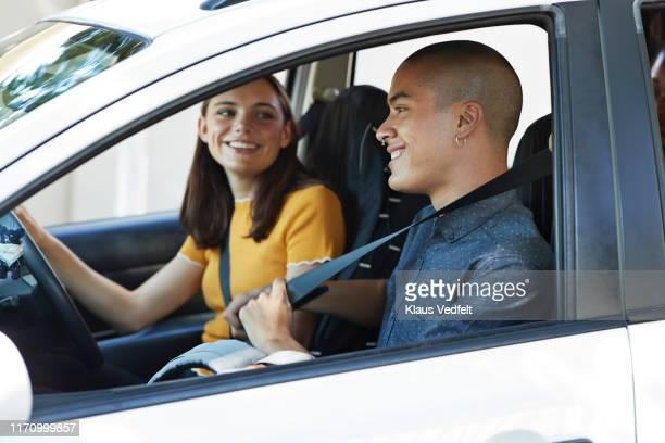 young woman looking at friend fastening seat belt - blauwe riem stockfoto's en -beelden