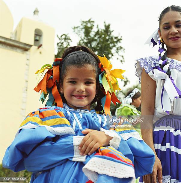 young woman looking at girl (5-7) wearing traditional dress, portrait - merida mexico stock photos and pictures