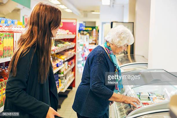 Young woman looking at grandmother shopping in supermarket
