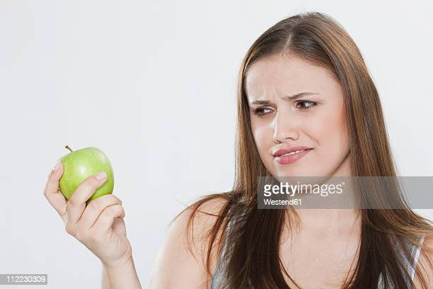 young woman looking at green apple - disgust stock pictures, royalty-free photos & images