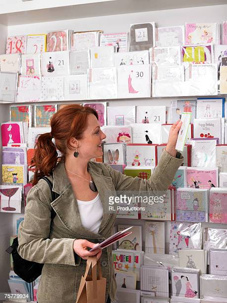 Young woman looking at greeting cards on rack, side view