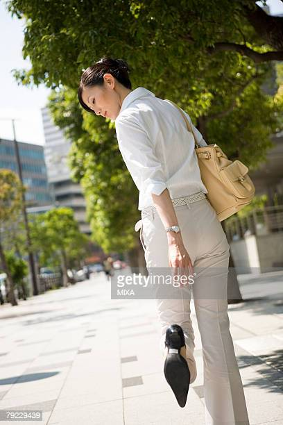 young woman looking at heels - standing on one leg stock pictures, royalty-free photos & images