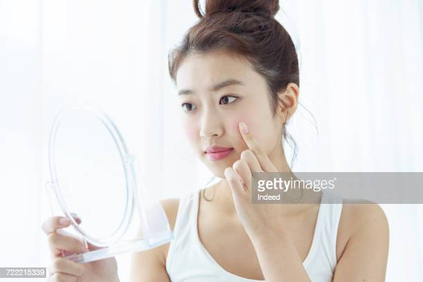 Young woman looking at her cheek in hand mirror