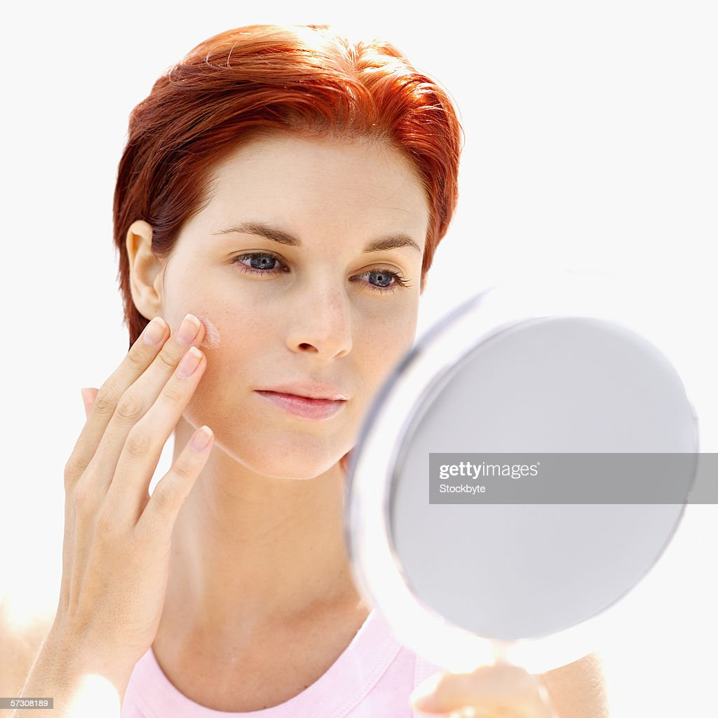 Young woman looking at her face in a mirror : Stock Photo