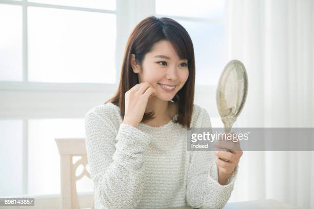 young woman looking at her face with hand mirror - hand mirror stock pictures, royalty-free photos & images