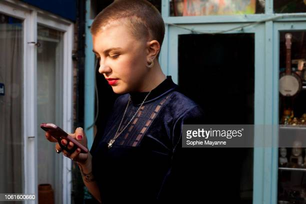 a young woman looking at her phone in the street - showus stock pictures, royalty-free photos & images