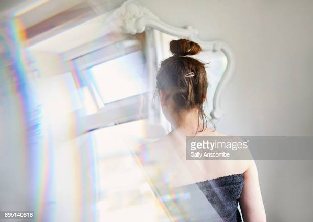 young woman looking at her reflection in the mirror - distorted image stock pictures, royalty-free photos & images
