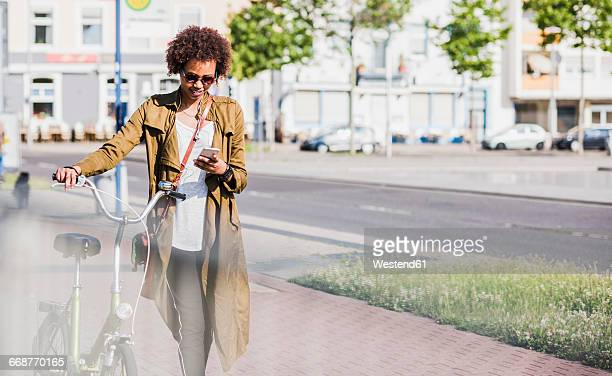 Young woman looking at her smartphone while pushing bicycle