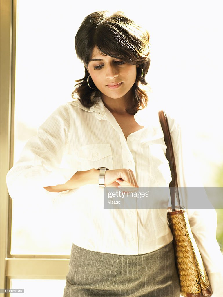 A young woman looking at her watch : Stock Photo