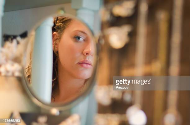 young woman looking at herself in the mirror - woman in mirror stock photos and pictures